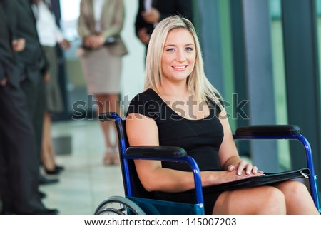 attractive disabled businesswoman sitting in a wheelchair - stock photo
