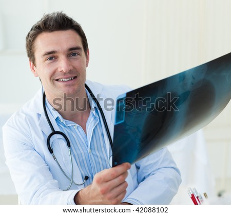 Attractive doctor examining an x-ray and smiling at the camera - stock photo