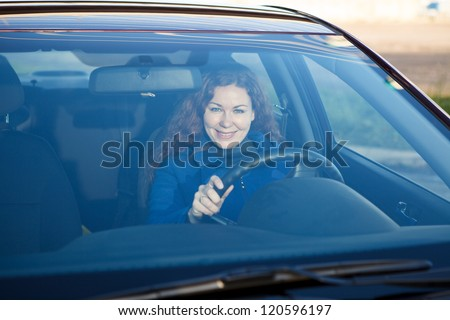 Attractive driver inside of car smiling through the windshield - stock photo