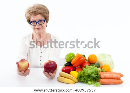 Attractive elder Caucasian woman holding two red apples, fresh vegetables and fruits are on table, white background - stock photo