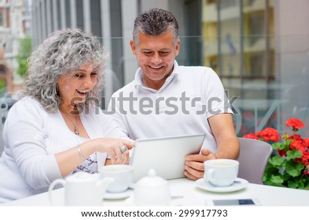 Attractive elderly family couple sitting in sidewalk cafe using tablet computer. - stock photo