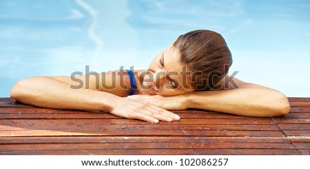 Attractive elderly woman resting at edge of swimming pool - stock photo