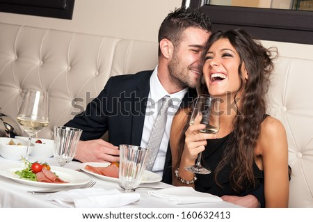 Attractive elegant young couple drinking a cocktail at the restaurant. - stock photo