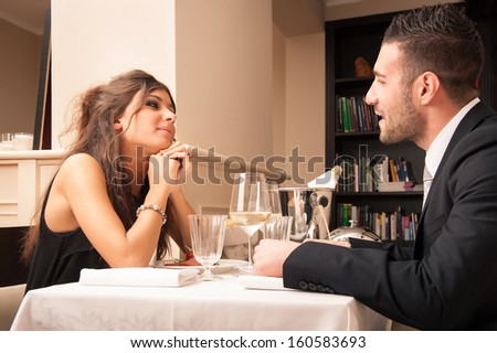 Attractive elegant young couple having dinner at the restaurant. - stock photo