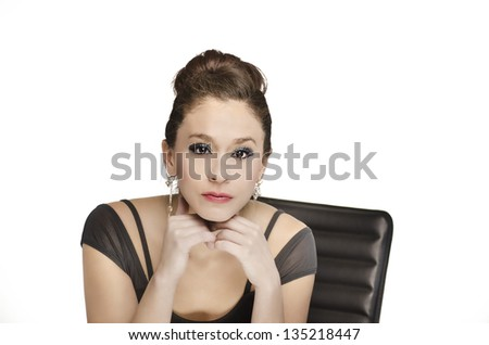 Attractive elegant young woman listening intently while sitting at her desk. - stock photo
