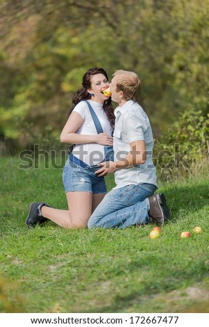 Attractive family in the park. Young man with his pregnant wife on open air - stock photo