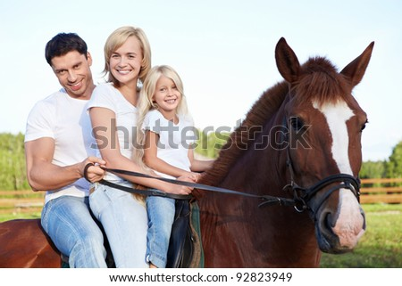 Attractive family on a brown horse - stock photo