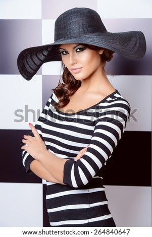 Attractive fashion model posing in dress in black and white stripes on a background of black and white squares. Beauty, fashion concept.  - stock photo