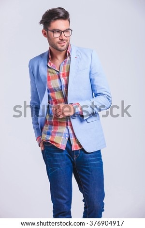 attractive fashionable man wearing glasses walking in studio background with hand in back pocket while looking away from the camera - stock photo