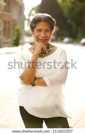 Attractive fashionable middle-aged woman standing in a street looking thoughtfully at the camera with a charming friendly smile - stock photo