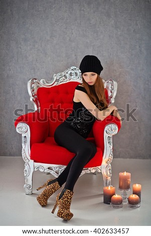 Attractive fashionable woman in black clothes sitting on a red chair. Candle stand on the floor. - stock photo