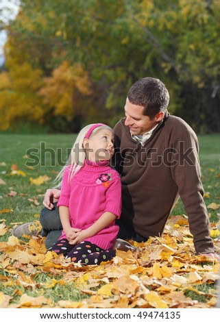 attractive father and daughter sitting in autumn leaves outdoors - stock photo