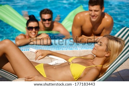 Attractive female and companionship by pool at summertime. - stock photo