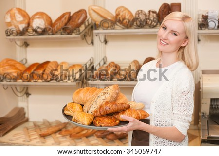 Attractive female baker is selling pastry. She is standing and holding the tray of buns. The woman is looking forward and smiling - stock photo