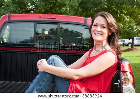 Attractive female brunette sitting in bed of red pickup truck. - stock photo