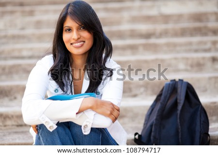 attractive female college student sitting outdoors - stock photo
