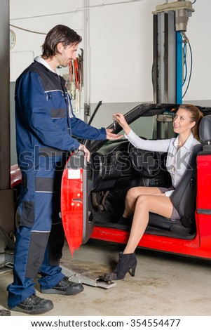 Attractive female customer is getting out of her car in a garage handing her car keys to the mechanic openig the driver door - stock photo