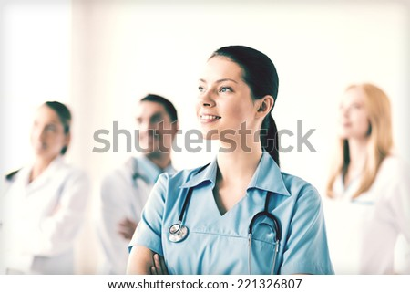 attractive female doctor or nurse in front of medical group - stock photo