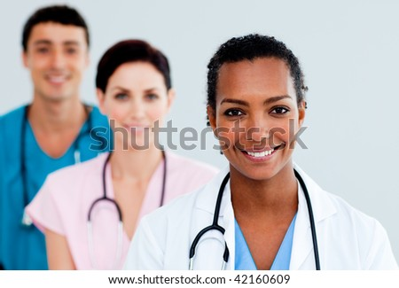 Attractive female Doctor standing before her team - stock photo