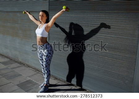 Attractive female doing warm up routine with dumbbells before start exercising, beautiful young woman in sporty clothing training bicep curls while lifting weights outdoors on copy space background - stock photo