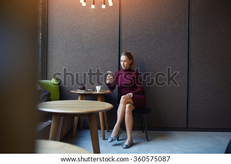 Attractive female dressed in elegant dress reading news via network on cell telephone while sitting in cafe, confident businesswoman using her smart phone while relaxing after work day in coffee shop  - stock photo