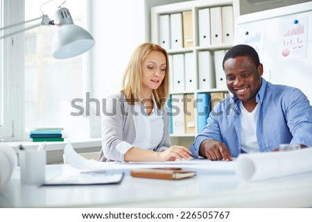 Attractive female employee pointing at blueprint with her African colleague near by - stock photo
