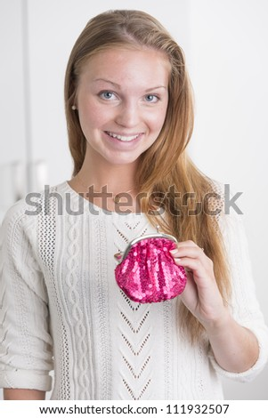 Attractive female holding pink wallet looking at camera and smiling - stock photo