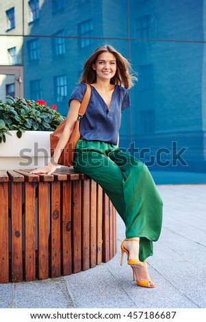 Attractive female in stylish elegant clothes is sitting on round bench with flower pot and posing at the camera in downtown - stock photo