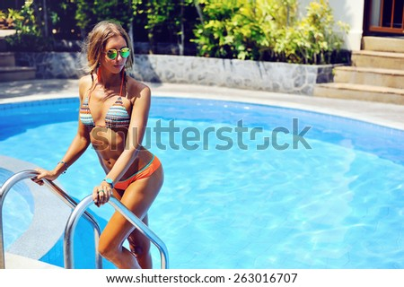 Attractive female model in bikini at the pool - stock photo
