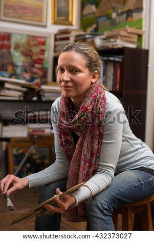 Attractive female painter sitting painting in a gallery holding a colorful artists palette and paintbrush in her hand and looking at the camera - stock photo