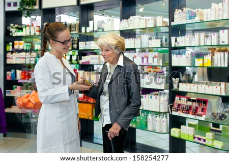Attractive female pharmacist helping a senior lady choose her toiletries offering her advice with a smile - stock photo