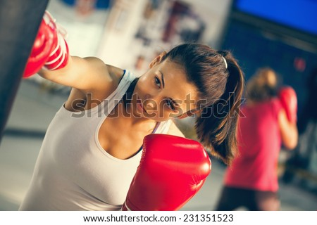 Attractive Female Punching A Bag With Boxing Gloves On - stock photo