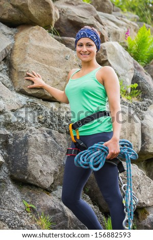 Attractive female rock climber smiling at camera leaning on rock face - stock photo