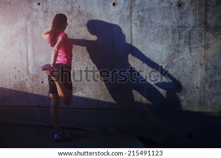 Attractive female runner stretching before her workout, young female sportswoman stretching and preparing to run, advertising for sports, fitness and healthy lifestyle concept - stock photo