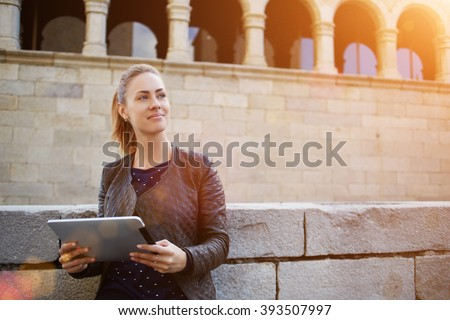 Attractive female student is dreaming about something, while is standing with digital tablet in hands against college. Thoughtful beautiful young woman is holding portable touch pad and looking away - stock photo