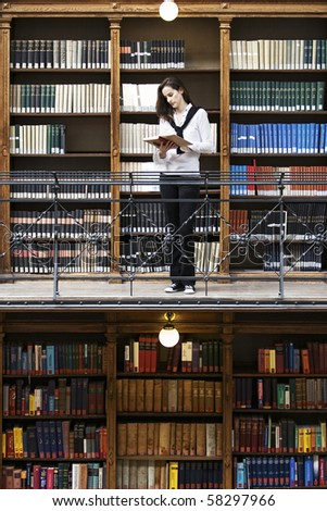 Attractive female student standing in front of bookshelf in old university library reading a book. - stock photo