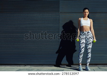 Attractive female taking break during her training with weights dumbbells, beautiful young woman in sporty clothing training bicep curls outdoors with copy space background for text message by side - stock photo