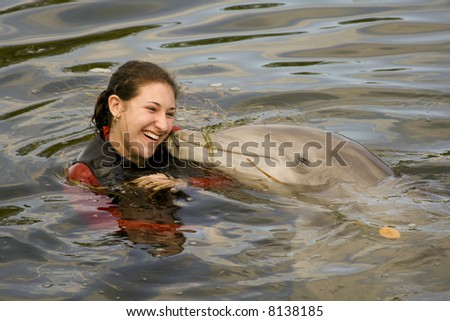 Attractive Female Teen is Being Kissed by a Bottle-Nose Dolphin - stock photo