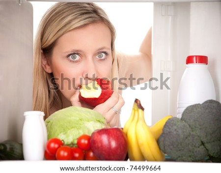 Attractive female teenager eating apple and looking at healthy fruit and vegetables in refrigerator. - stock photo