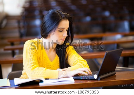 attractive female university student using laptop in classroom - stock photo