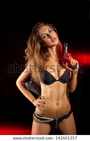Attractive female with pistol on black background in studio - stock photo