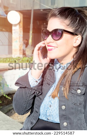 Attractive female with smile on her face communicate on her cell phone,selective focus  - stock photo