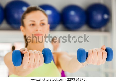 Attractive Females Doing Step Aerobics Exercise With Dumbbells In A Gym. Focus Is On Dumbbells. - stock photo