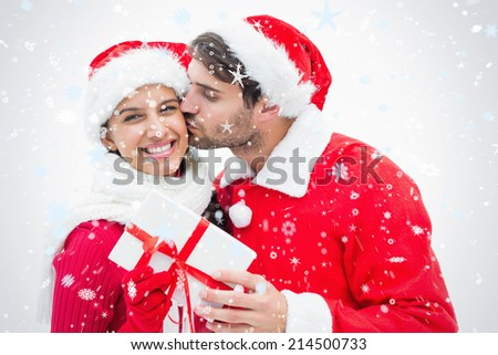 Attractive festive man giving girlfriend a kiss and present against snow falling - stock photo