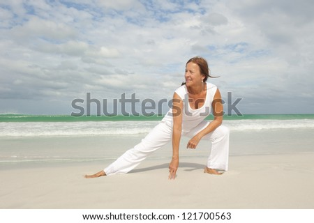 Attractive fit and healthy middle aged woman doing stretch exercising confident and happy at beach, isolated with ocean and cloudy sky as background and copy space. - stock photo