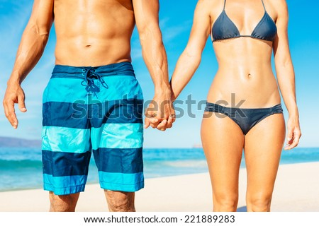 Attractive Fit Couple on the Beach in Swimwear Holding Hands     - stock photo