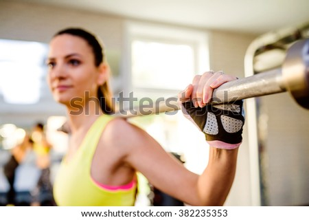 Attractive fit woman in gym exercising with weights - stock photo
