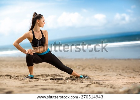 Attractive fit woman stretching  on beach, outdoor workout - stock photo