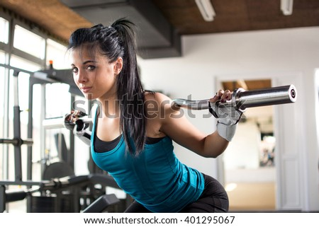 Attractive fit woman working out with barbells in gym. - stock photo