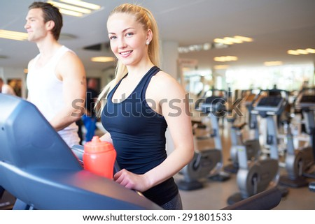 Attractive Fit Young Woman Smiling at the Camera While Exercising on Treadmill Device Inside the Fitness Gym - stock photo